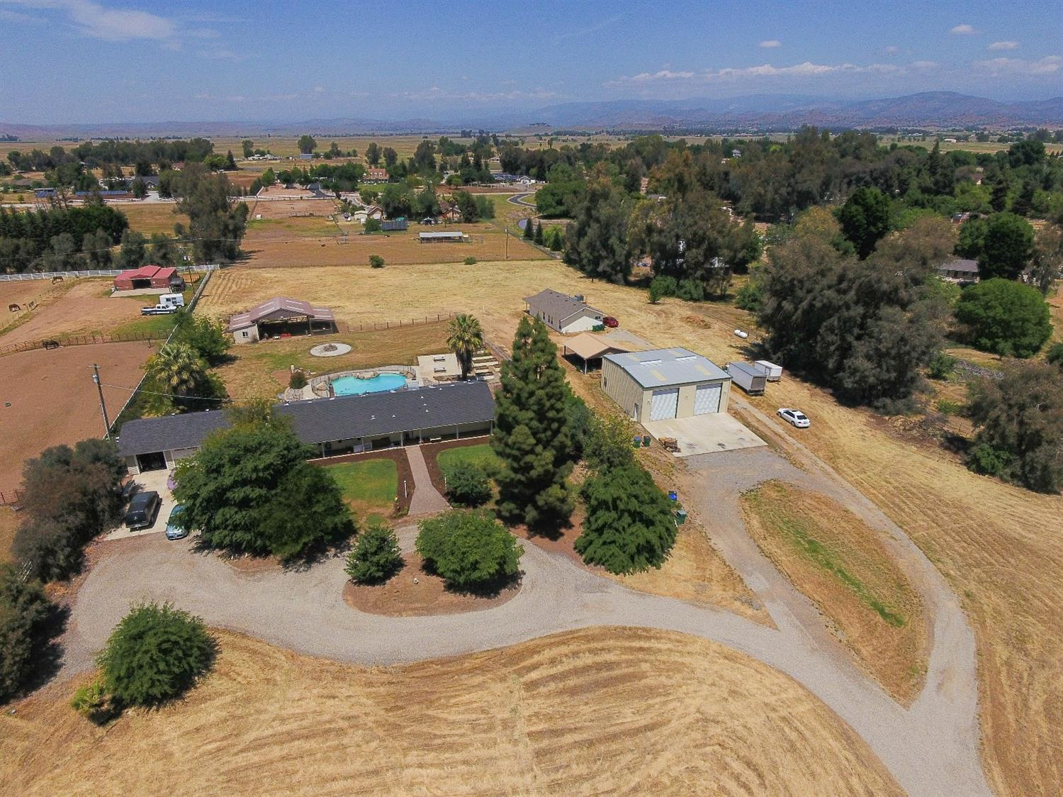 2 Homes on 4 77 acres. Clovis School District. Horse Property! Very tranquil area on non busy street. All the amenities you could dream of! Main house is 4 bedrooms, 2.5 baths, 2310 sf. Enter into the great room with sunny views to the large pool. Nice corner fireplace for cooler nights. Kitchen fully remodeled. Open concept. There is also a family room and bonus room. Oversized bedrooms, hickory wood floors, carpet in bedrooms. New 3 car garage. 2nd home built in 2016, 2 bedrooms, 2 baths, 1280 sf, granite counters, wood floors, walk in showers, wood shutters. Great for extended family or other use. Separate utilities and meters. Pole barn, stables, fire pit and patio for evening enjoyment. Anlin windows, 40x40 Borga Shop, fully insulated, w/ 12 ft heavy duty roll up doors w/30 ft of concrete. Property fully fenced. Well:28 gpm, water at 44, pump at 105 ft. Constant Pressure System, 2500 gallon holding tank.  Priced low to sell quick!  Hurry before it is gone!