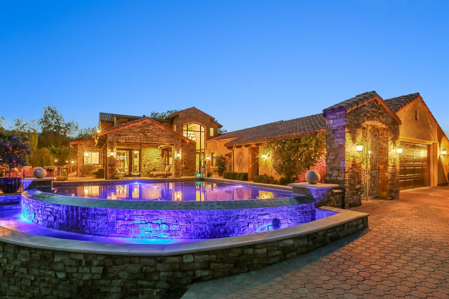 Luxurious estate set on 20 acres in the foothills of Lemon Cove! This home features breathtaking views of the Valley, while it sits in the quiet privacy of the Kalamata olive trees that surround the estate. The outdoor kitchen, infinity pool, pool bath and wine cellar dug into the hillside under the home are just a few of many amenities. The large kitchen is equipped with a commercial grade stove, three ovens, warming drawer and built in refrigerator and freezer. There is a large granite island with a prep sink and and ice maker. The oversized butler's pantry has a second dishwasher ,a second refrigerator. with counter tops for plating food and plenty of storage. The living area has a spectacular stone fireplace, dining room and lounge area are perfect for a quiet evening or to entertain a large group. The two story entry is stunning.. The gorgeous closet in the master is breath taking and has it's own ''shoe room''. The thousands of sq ft rock patio set off the magnificent Valley view