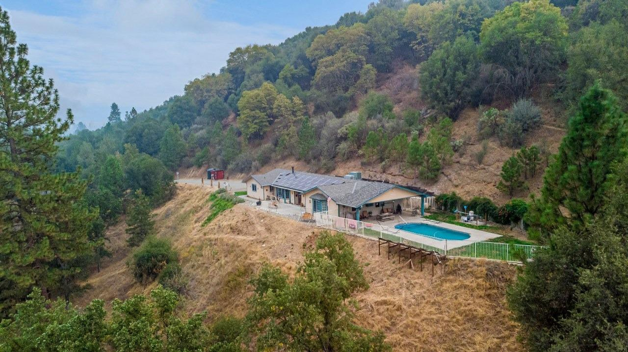 Take a look at this beautiful 3 BD, 3 BA, 2170+/- sq. ft. home on 6.02+/- acres with a beautiful 180 degree view of the Yosemite & surrounding Mountains! The home is gated & private, has a very nice in-ground pool & is located a block from the River Creek Golf Course in Ahwahnee. If you like an open floor plan, you will love this single-story home with a large vaulted open area great room with a custom wood-burning stove to enhance the ambiance of the beautiful vista views. The great room also has a drop-down remote control projector & screen to enjoy your favorite movies. The kitchen features all new stainless steel GE appliances, a granite double farm sink, custom counter tops & more. The extra-large master suite has 2 master closets, new