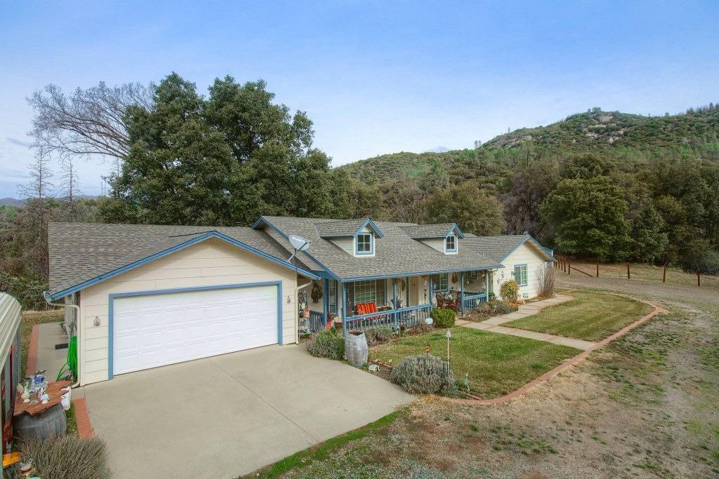 If you are looking for a place to call home, living in peace and serenity with beautiful pines, oaks and cedars and close to both Mariposa and Oakhurst, look no further! This home is a dream come true! Gorgeous private setting with panoramic views, year 'round creek and plenty of room for horses. This 2135+/- sq. ft. 4 bedrooms, 3 bathrooms has separate living room and family room, with built-in book cases, open kitchen, separate spacious laundry room, tile floors throughout, free standing wood stove, large covered porch in both front and back with outdoor ceiling fans, plus appx. 600 sq. ft. steel building with bathroom, possible guest home, permitted as storage, all on 5.5+/- acres with 2800 elevation. Includes a large fenced-in orchard w