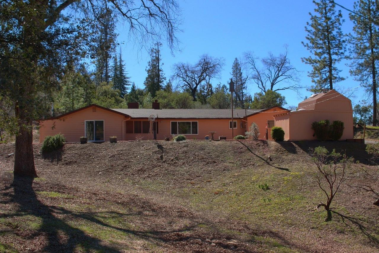 Wonderful remodeled 1689+/- sq. ft. home sitting back on 1.41+/- acres with fruit trees, along with lots of pines, oaks and cedars. The front has over 500 irises in the terraced yard to view when in bloom. Also has a fenced garden in the back. Large outdoor patio with 2 car garage and separate/storage building plus 2 RV water and electrical hookups! This 3 bedroom, 2 bath home has an open floor plan with large kitchen and granite counters, pull out drawers and lots of cabinets, 2 pantries and plenty of space to entertain from. One of the bedrooms has a built-in Murphy bed. New comp roof and rain gutters. New heat/AC unit. New exterior paint, new hardy plank siding, back yard raised gates, new window coverings, Casablanca programmable fan/li