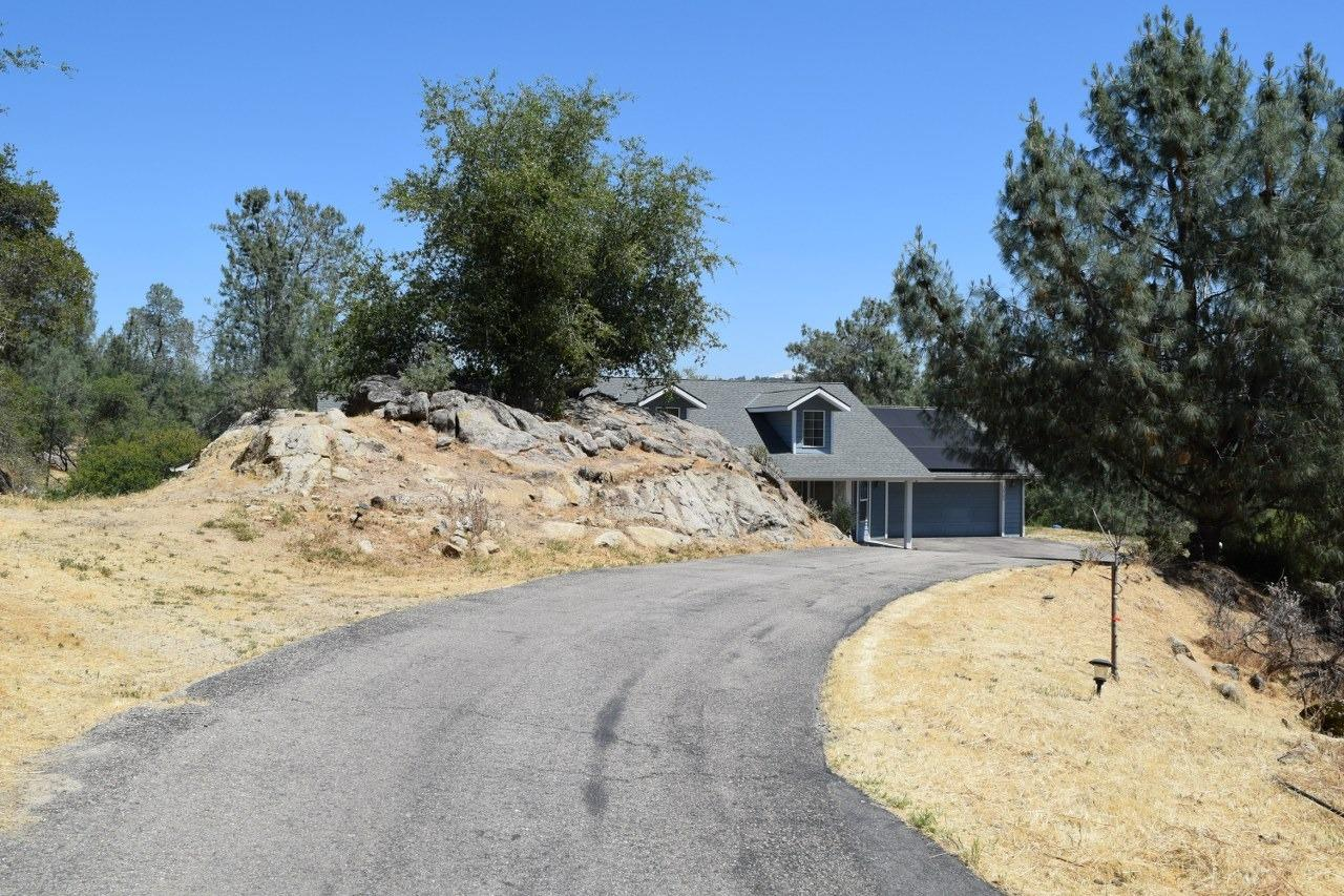 Welcome to this beautiful custom home in Yosemite Lakes Park! Lots of windows and natural light on a corner lot. As you drive up the paved driveway you will see beautiful dormers and a covered patio with recessed lighting. This 1849+/- sq. ft. home offers 3 bedrooms and 2  bathrooms with fully owned solar panels! Custom kitchen with granite counters, Bosch stainless steel appliances, propane oven with convection for all your cooking needs. Underneath the kitchen sink is a water drinking filtration system, custom cabinets, and extra storage in the room adjacent. This home offers RV parking with clean out system as well as mature oaks and rocks surrounding you. Located in Yosemite Lakes Park with lots of amenities including golf course, commu