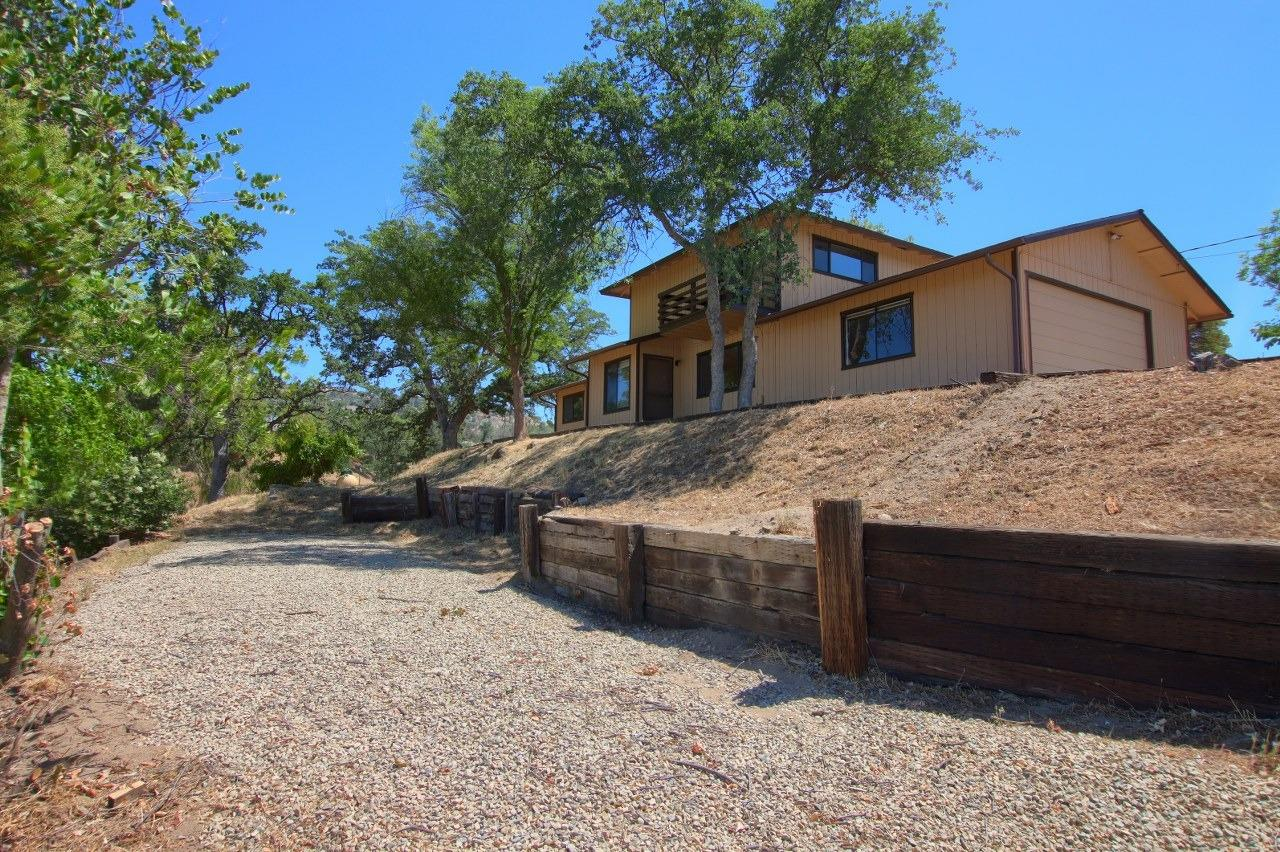 This adorable 3 bedroom, 2 bath has 1572+/- sq. ft. and sits on an open 1.34+/- acres!  Custom built 1988 two story home, sitting on top of a knoll with great views, is ready for you.  Living room is open to the kitchen with an electric range, dishwasher, disposal, breakfast bar and a separate dining area.  Upstairs is the master suite with a nice balcony that is perfect to enjoy your morning coffee or a glass of wine in the evening.  There's place for an RV or a boat.  Freshly painted interior and new flooring throughout.  2 sheds and a 2 car garage with a nicely paved long driveway.  Yosemite Lakes Park amenities include golf, swimming pool, spa, tennis court, equestrian center, hiking and riding trails, fishing, clubhouse and more!