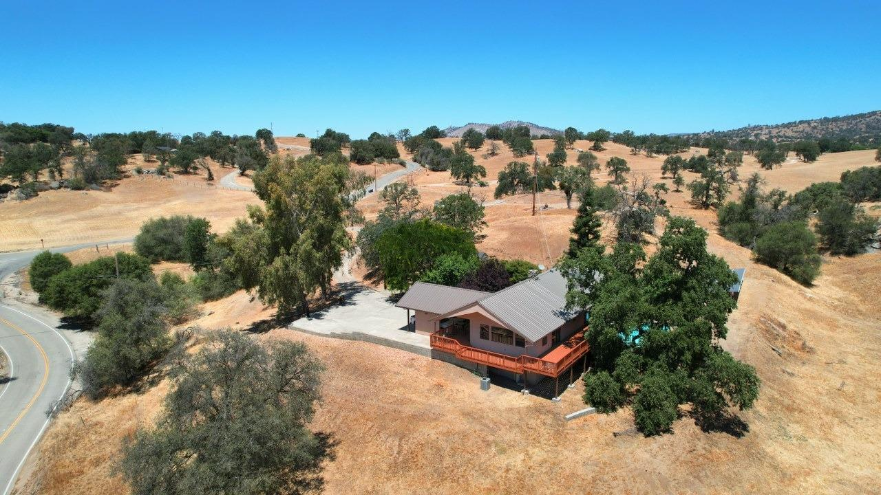 Dream home in the Clovis Foothills. Are you looking for a large and spacious family home in a peaceful setting? How about 360 degree views? Well this may be the one! Beautiful custom 2900+/- sq. ft. home with 4 bedrooms, 3 bathrooms sits on just over 9 gorgeous all usable acres. Impressive kitchen is open to the living room and family room.  Remodeled in 2011, truly a cook's delight with plenty of room to entertain from with 3 ovens, trash compactor, dishwasher, self-closing cabinets, RO system, water softer, recessed lightening, 2 breakfast bars, and rolling island. Separate dining area. Master bedroom and bath are on the main floor along a guest bedroom. Living room has a large rock fireplace, surround sound throughout, Walk down to the s