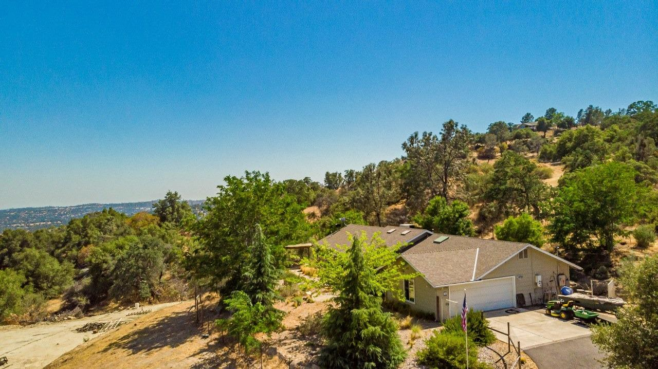 Owned Solar! Situated on 1.4+/- acres with mountain views this 2,178+/- sq. ft. home built in 2003 offers 4 bedroom, 3 bath, with a spacious open floor plan great for entertaining.  Wonderful natural light through skylights brightens this home. The great room features an attractive shelving unit that accents the main wall, vaulted ceilings, pellet stove, LVP Luxury vinyl plank floors, and skylights. The kitchen that opens to the dining area and great room features stainless steel appliances, a breakfast bar, and walk-in pantry along with stunning granite counter tops that offer plenty of space for prepping your favorite meals. You won't have to compromise on choosing between a guest bedroom or a home office since this floor plan offers a 4t