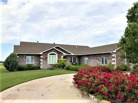 Enjoy country living in this beautiful 5,800 sq ft ranch style home with walk out basement sitting on 5 acres. Entire home built with 18 inch eco-block walls w/ brick surrounding it.  Home has 4 bedrooms & 4 1/2 bathrooms. Upstairs master bath is equipped with jacuzzi tub, large walk-in closet with laundry hook ups. Walk out of the master onto your balcony which spans the entire width of the house. Surround sound throughout main level & outside deck area. Kitchen has beautiful custom cabinetry, 2 convection ovens with warming drawer and a large walk in pantry. Family room has custom roman shades with gas burning fireplace. Relish in your walkout basement with 9 foot ceilings, all new carpet throughout, large wet bar and wood burning fireplace. There is also laundry hookups in the basement. The triple car heated garage boasts a heated driveway and garage  floor.  Enjoy your evenings watching the sunset on the deck, looking at the beautifully landscaped rocks brought in from Colorado.