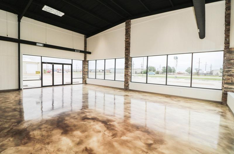 This versatile property was originally built to be a auto sales/oil change facility, but boast a versatile design that allows it to be suited for a variety of uses. Spectacular showroom with beautifully custom finished concrete floor you have to see to appreciate. Space could easily be converted to retail front with inventory storage, package store with drive thru bay, just to name a few. Large concrete parking lot (50,000 sf),Back lot fenced security area. 5800 grd floor with combination office showroom shop area and versatile office space. Large warehouse area with (5) 14' Doors and drive through center section. Also has a 1200 sq ft loft over the office section with storage for inventory and upstairs office for shop/warehouse manager.  Entire building has hard cell foam insulation and the building is serviced by its own premises private well.