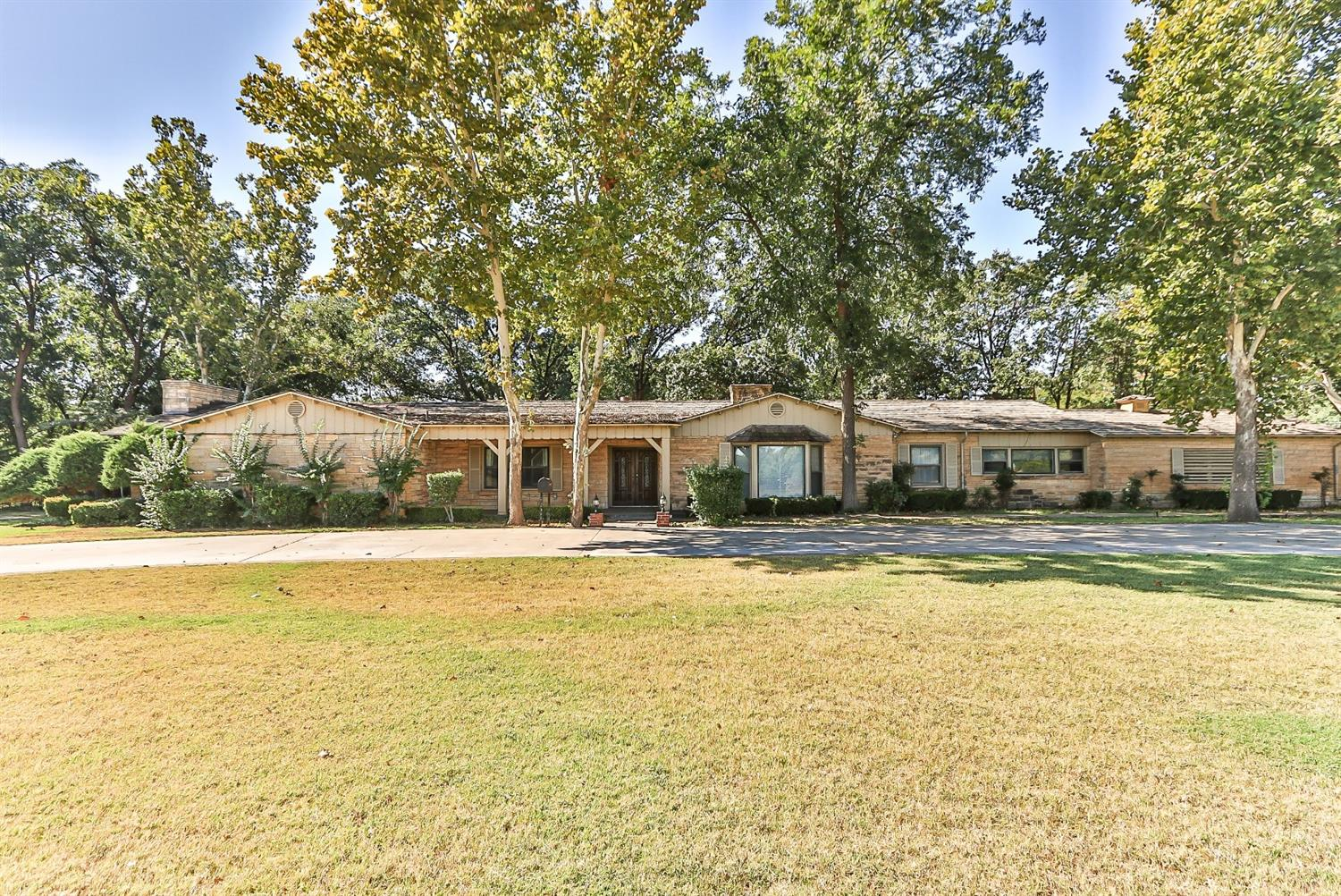 Welcome to a  Grand Vintage Ranch style home in prestigious Bobalet Heights on nearly 2 acreas. This is the one you have been waiting for. Use your imagination and create your dream home.  The main house has 3225 sq feet with 4 beds, 3 baths and 4 garages with carports for 4 cars. and a 594 sq foot 2/1 Apt. on the back of the lot. One of the living areas has built-ins that would be great by a dining table and a second great room has a bar in the corner. This spacious home is located on a corner lot with a circle drive; a pool and decking with separate dressing areas.  A water well for the large yard a garden area with multiple pecan trees.  2 garages could make a perfect workshop. Make this incredible home yours today!