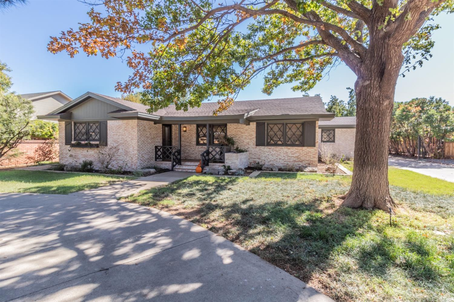 This modern French Country home is located on the BLVD of Lubbock--19th Street. The freshly landscaped yard and abundance of parking is perfect for those looking for a garden home and/or those looking for a low maintenance single family home. A 3/2/3 with gated drive to parking and fully equipped guest house--truly a gem!  The main house features a chef's kitchen with WOLF stove and ovens, a custom oversized island, and sleek built-in side-by-side fridge & freezer complete this dream kitchen.  Soaring vaulted ceilings in the living and kitchen areas have custom wooden beams with matching fireplace mantel.  The large master suite features a gorgeous walk-in shower and freestanding tub, double vanity with quartz, and his and her closets.  There is ample parking in rear as well as circle drive up front. Exterior of home is adorned with custom ironwork including the soon-to-be fully automated private gate to garage and rear parking. Low Voltage landscape lighting looks terrific at night.