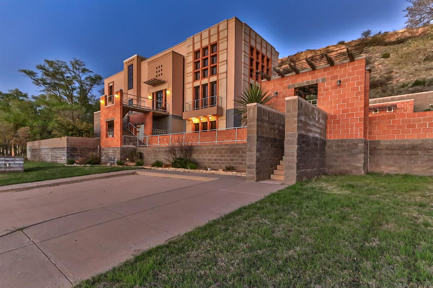 Walk from this amazing southwest contemporary home across the road to Lake Ransom Canyon! The main master suite encompasses the third level, offering private living area, over-sized bedroom w/fireplace & Juliet balcony. The en suite boasts two dressing areas, skylight, spa tub, steam shower, two closets & abundant storage. The kitchen has separate Sub Zero refrigerator & freezer, two ovens, ice maker, wine fridge & large pantry. The second master suite has a large closet, separate shower, Kohler soaking tub & is designed to allow for privacy while being utilized as a guest half bath. The third bedroom overlooks the pool & the lake. Its three-quarter bath may be accessed by guests enjoying the pool fireplace on cool nights or a relaxing swim in summer with the  fountains splashing! The 3 car garage has a 10x12 workshop & a 9x10 closet. Unbelievable storage. The unique features must be seen in person to truly appreciate! South lot can be purchased separately. Call today & fall in love!