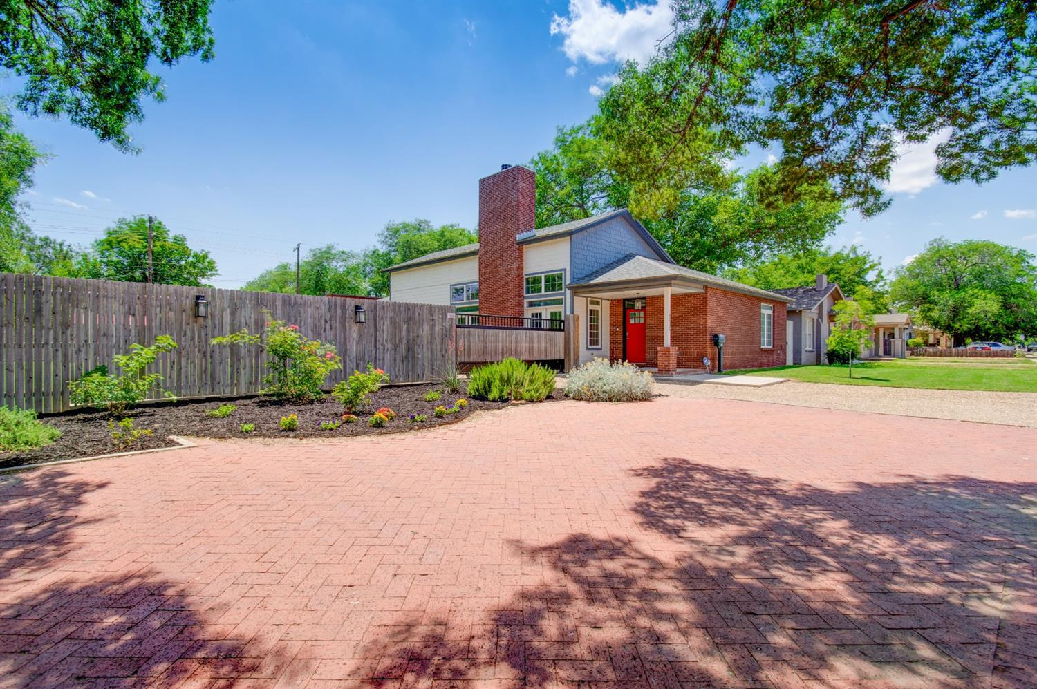 This custom home was built in 2017 on two lots, that are separate parcels, making this listing the most versatile and exciting  property in Tech Terrace. The soaring 10 ft ceilings in the family room with a cozy fireplace and stained concrete floors, make this a perfect family home, Texas Tech rental, or AirBnB Oasis. The connecting lot next door could be a phase II of wherever your imagination takes you! Its all tucked in behind a 7 ft. privacy fence with an electric gate, and covered RV parking with hookups. There is a safe room engineered by the Tech wind department, and more storage than you have EVER seen. This house is something to see!