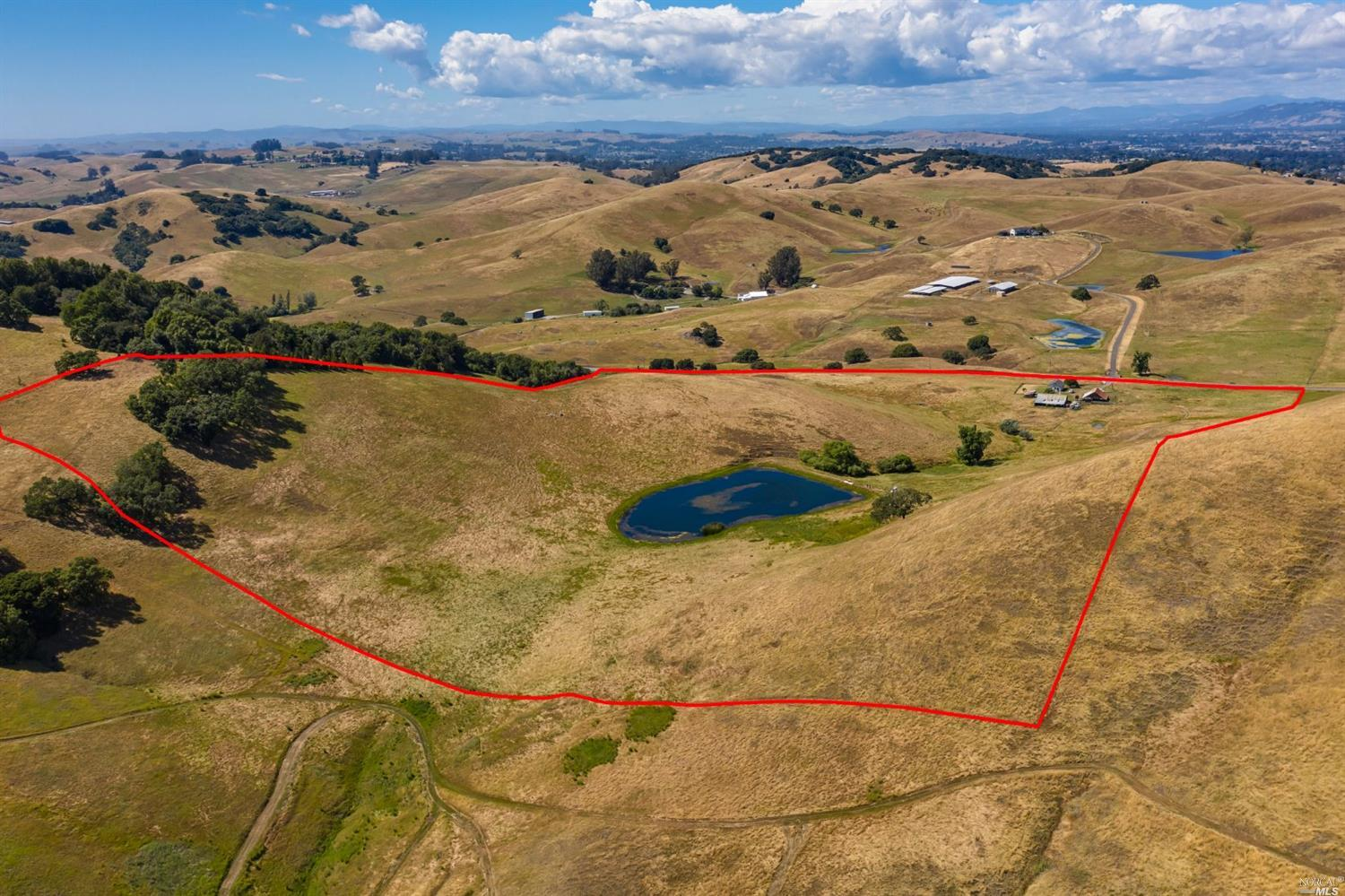 56 beautiful acres less than 4 miles to downtown Petaluma.  A variety of terrain presents endless possibilities, with level acres close to D Street, ascending to beautiful hills along the southern portion encompassing a man-made pond with excellent bass fishing.  Ample opportunities for agricultural endeavor, farming, and ranching, with 2 barns on property.  Also present is a well-maintained older home.