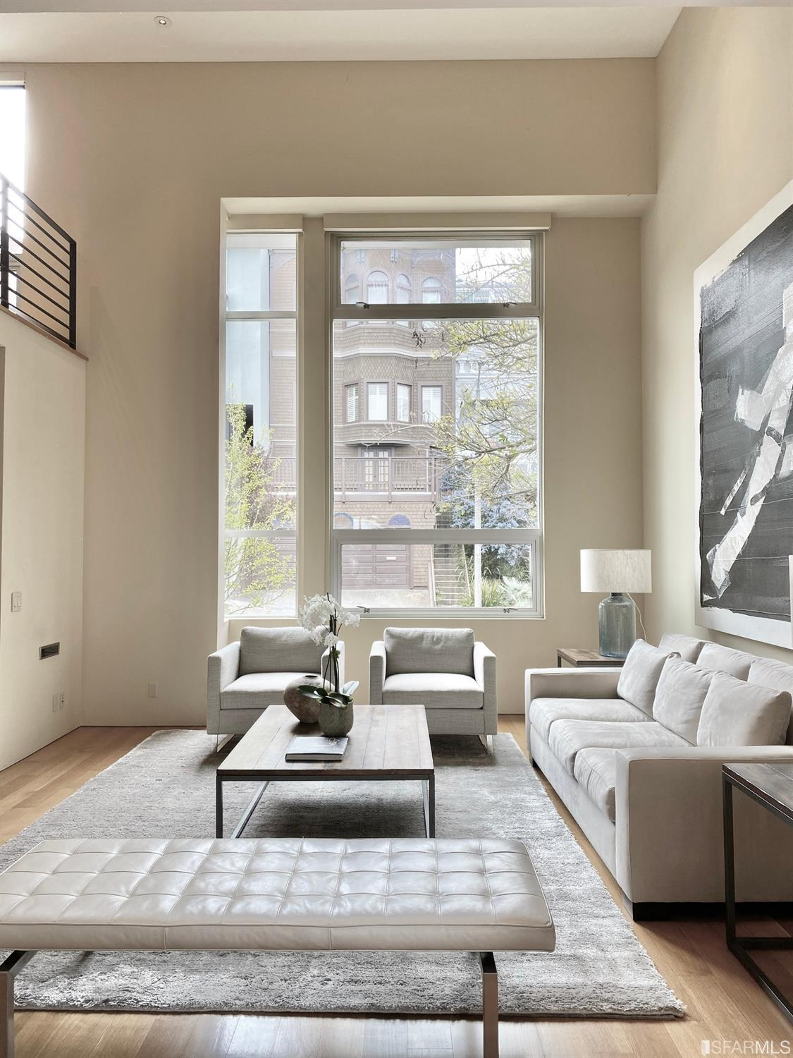 Dramatic living room with double height soaring ceiling, huge picture window and catwalk at upper level