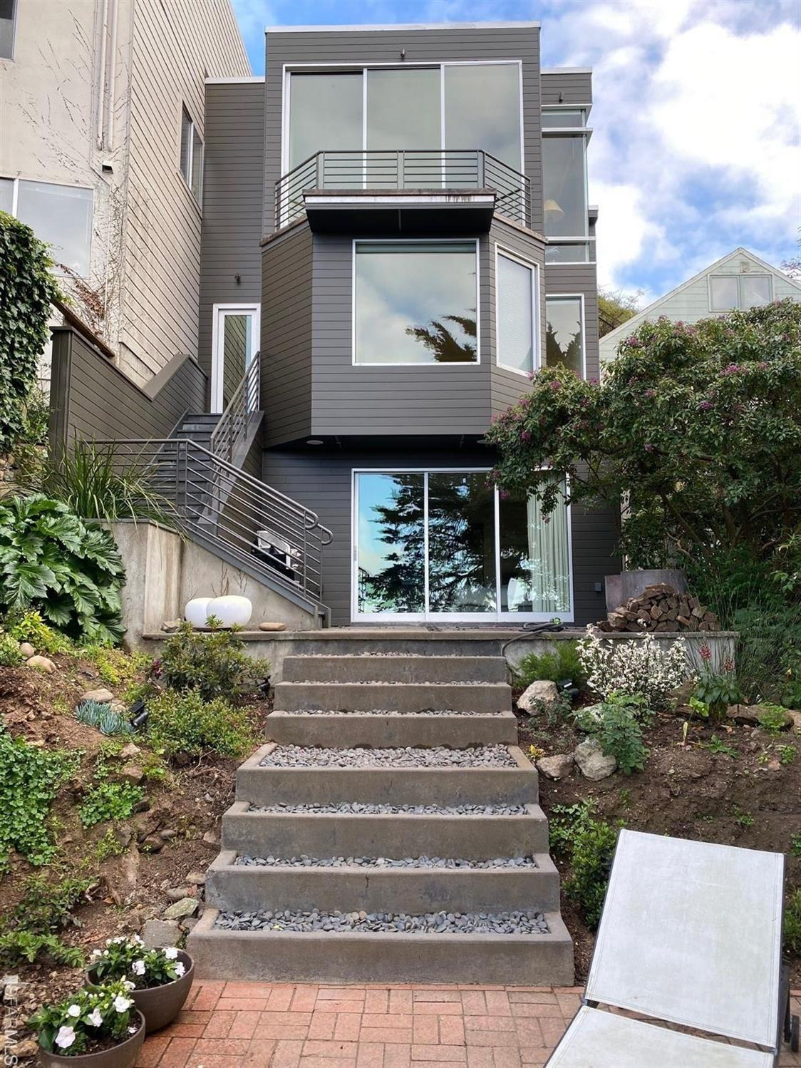 2 patios and the landscaped garden at the rear of the contemporary residence with huge picture windows and sweeping views from a