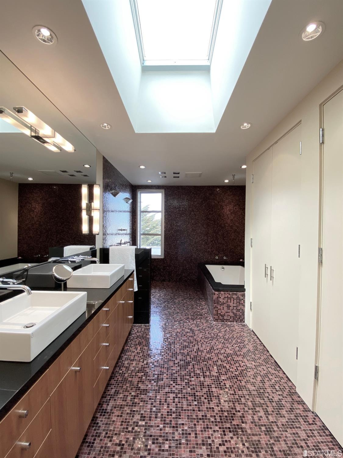 Master bath with double sinks and granite counters, large shower, and soaking tub and large skylight. Adjacent to the bathroom i