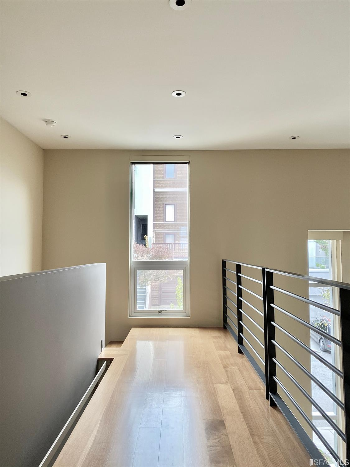 Dramatic upper level catwalk overlooking the double-height living room, and leading to the large master suite