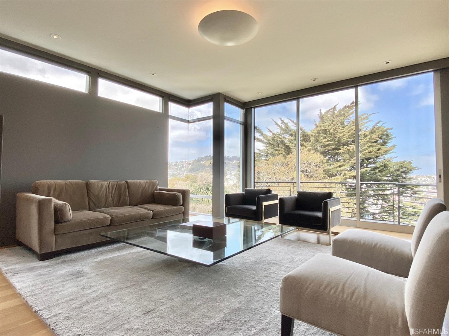Family room with floor-to-ceiling windows, Fleetwood telescoping door to a deck, and expansive views of downtown and sweeping no