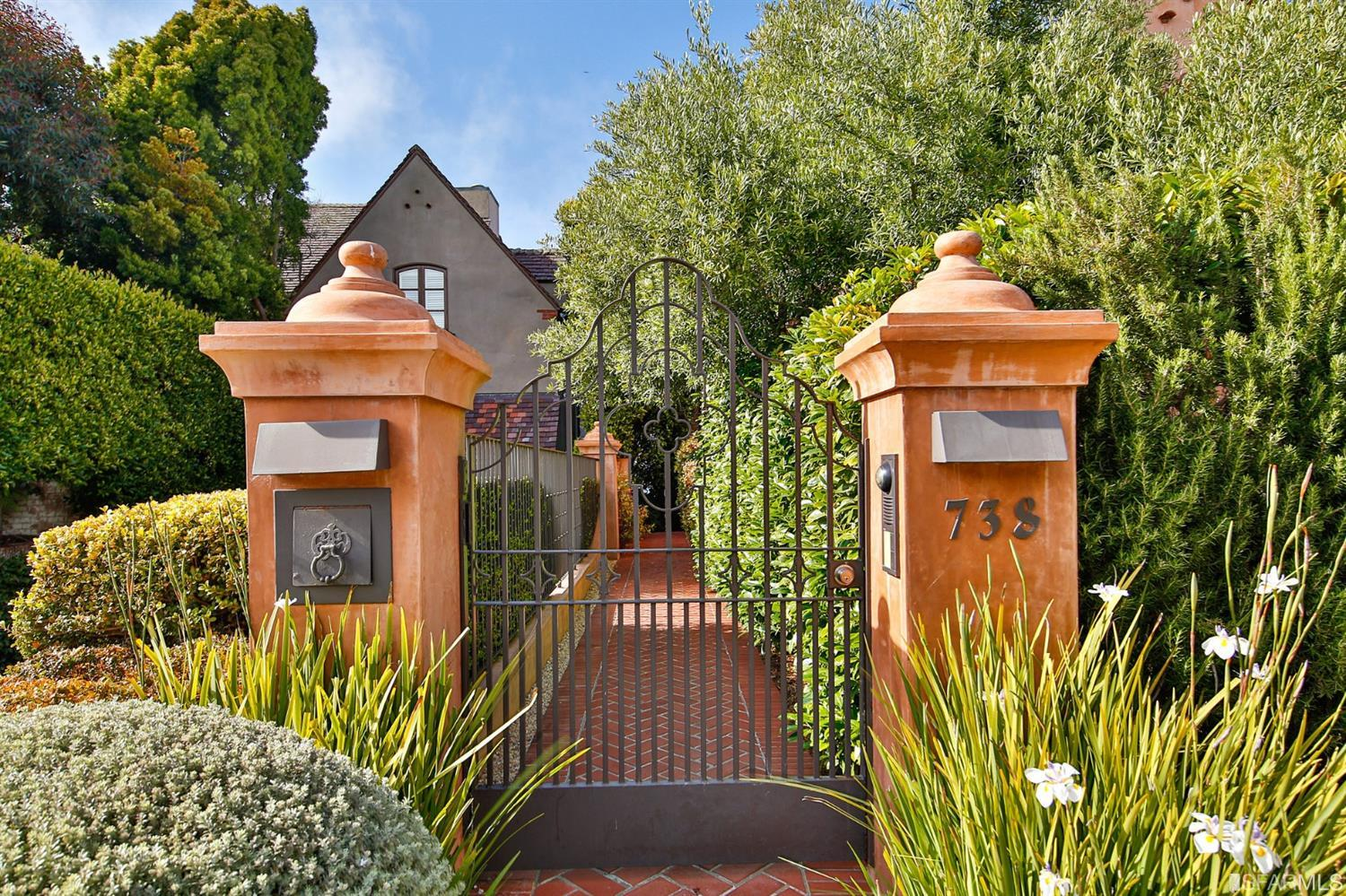 This striking wrought iron gate offers privacy for the owners.  The brick pathway leads past the front garden to the entry - so